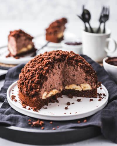 Ein selbstgemachter veganer Schokoladenkuchen angeschnitten und angerichtet auf einem weißen Teller auf dunklem Hintergrund