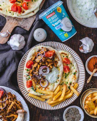 Veganes Gyros aus Pilzen mit Pita-Brot und Tzatziki angerichtet mit Pommes und Tomaten auf einem flachen Teller und hülzernem Untergrund