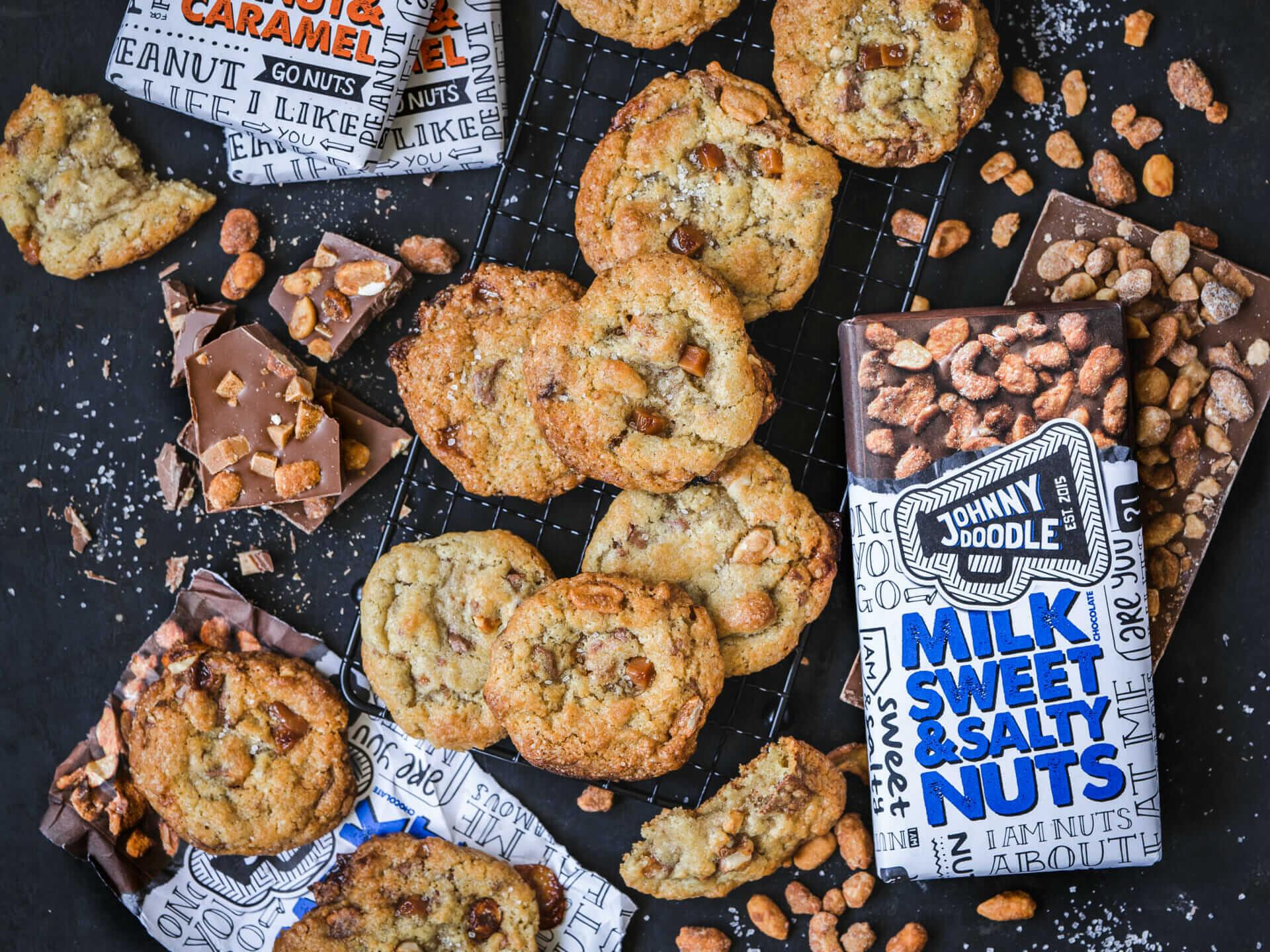 Kekse mit Schokoladenstückchen, daneben verschiedene Sorten Schokolade von Johnny Doodle