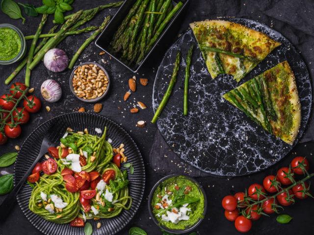 Bunte Platte aus Nudeln mit Pesto, Tomaten und Spargelpizza - angerichtet auf dunklem Hintergrund