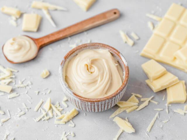 Weiße Schokoladencreme in einer kleinen Schüssel, daneben ein Holzlöffel und zerbröselte, weiße Schokolade