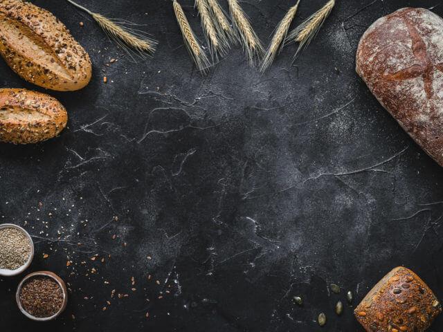 Brot, Brötchen, Getreide und Samen auf dunklem Untergrund