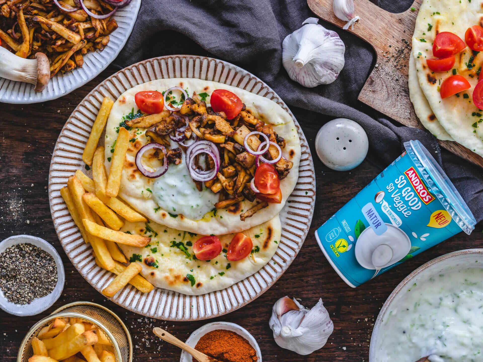 Pita, Gyros, Tzatziki und Pommes angerichtet auf einem Teller und hölzernem Untergrund