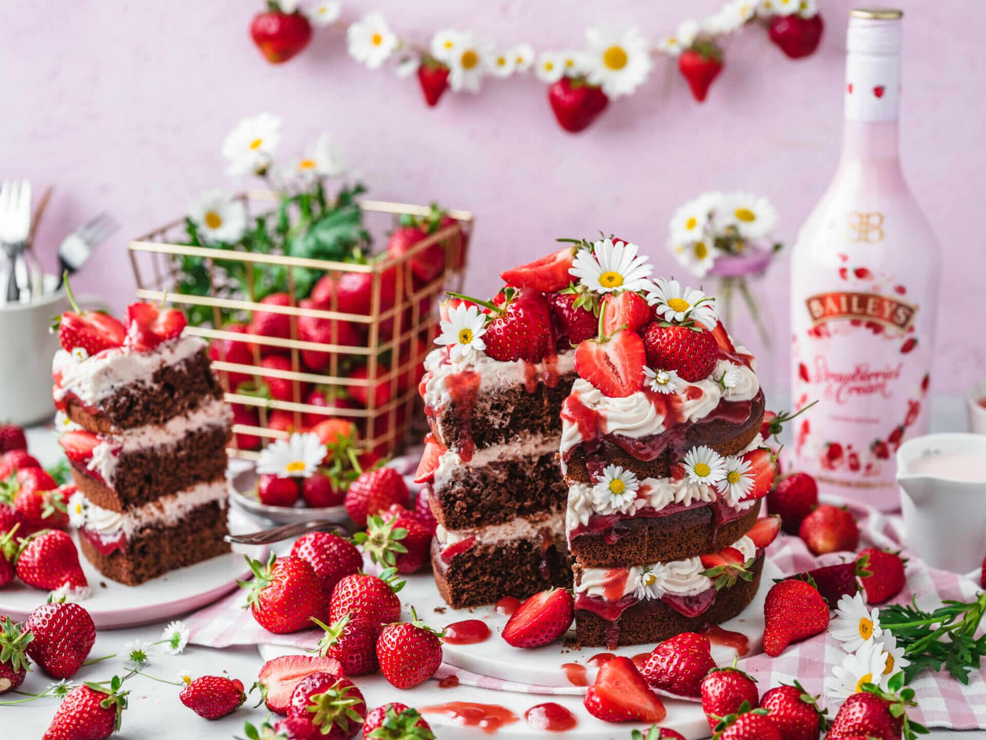 Dreistöckige Schokoladentorte dekoriert mit Erdbeeren und einer Flasche Baileys im Hintergrund