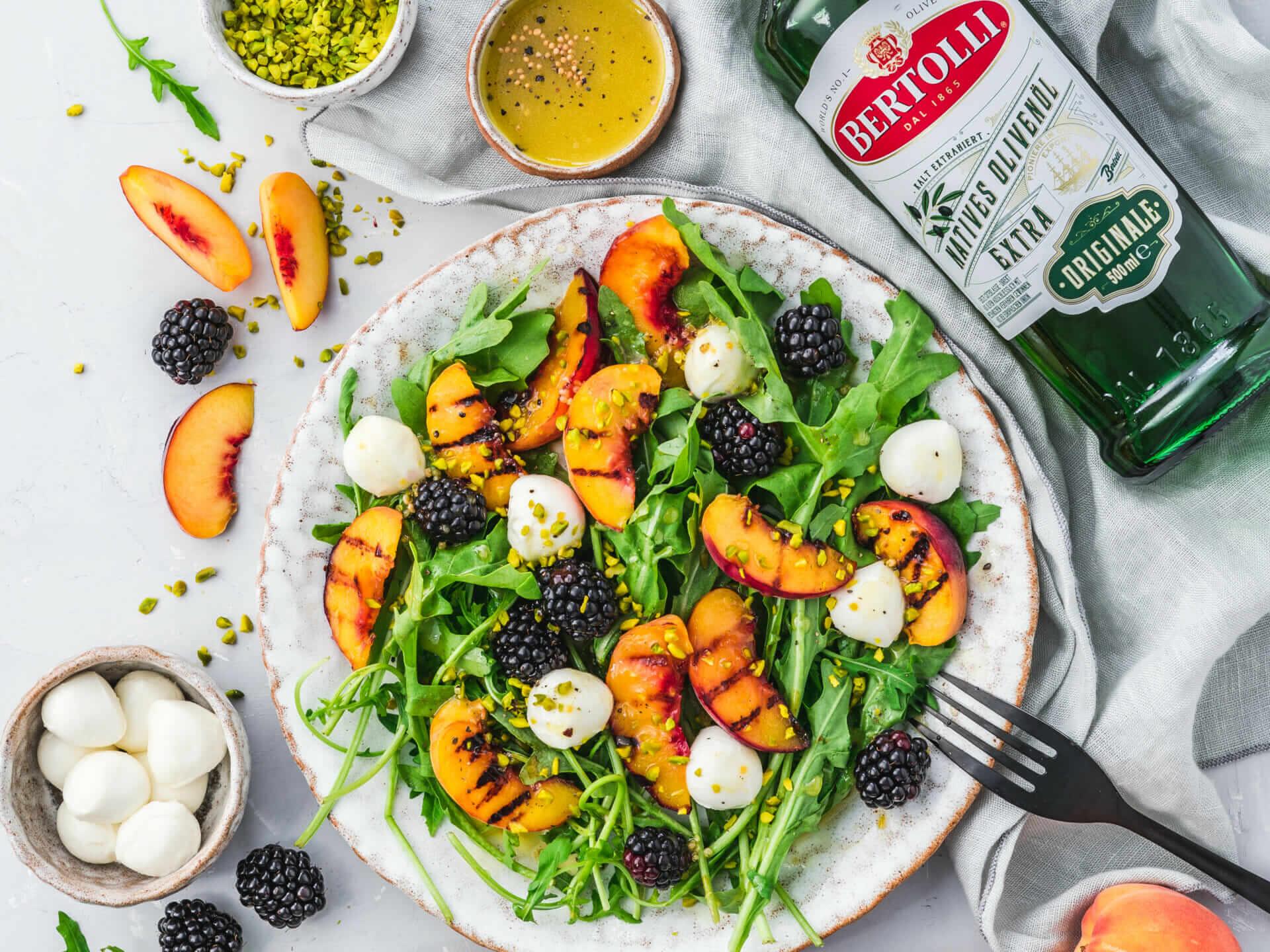 Rucolasalat mit gegrilltem Pfirsich, Mozzarella und Brombeeren - daneben eine Flasche Bertolli Olivenöl