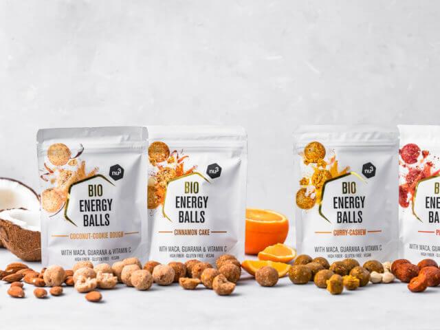 Vier Packungen Energy Balls von nu3, dekoriert mit Nüssen und Orangen
