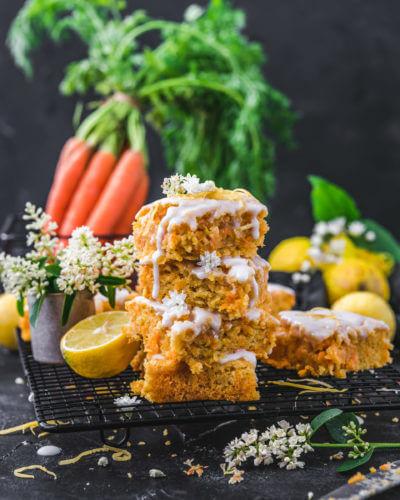Mehrere Stücke des veganen Karottenkuchens aufeinandergestapelt und mit Zuckerguss garniert, angerichtet auf einer dunklen Marmorplatte und dunklem Hintergrund