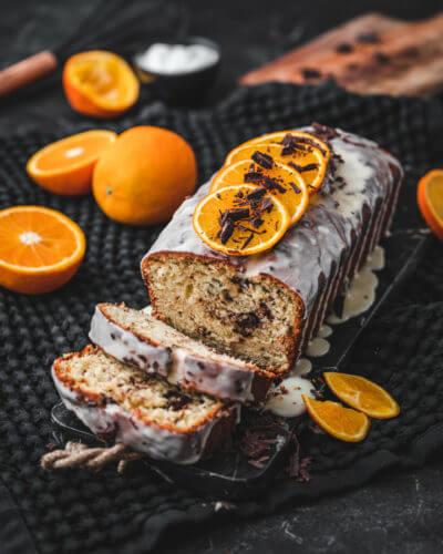 Ein angeschnittener Stracciatella-Kuchen mit Zuckerguss, Schokosplittern und Orangen dekoriert auf einem Marmorbrett
