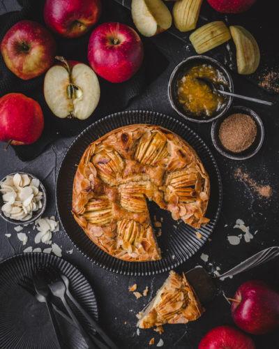 Angeschnittener Altländer Apfelkuchen auf dunklem Hintergrund in der Vogelperspektive mit vielen roten Äpfeln drumherum