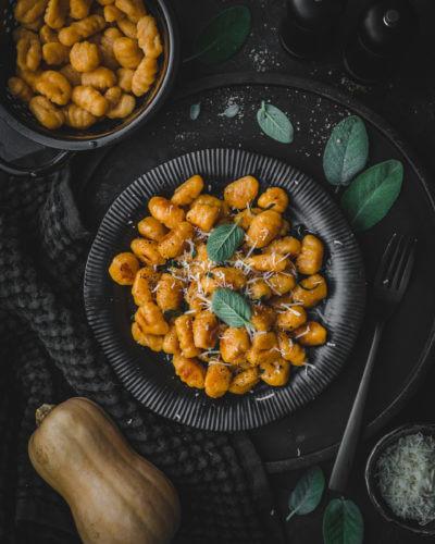 Ein schwarzer Teller mit Kürbis-Gnocchi in Salbeibutter auf schwarzem Untergrund, im drumherum zwei schwarze Pfeffermühlen, ein schwarzes Sieb mit frischen Kürbis-Gnocchi, eine kleine Schüssel mit geriebenem Käse und ein Butternusskürbis