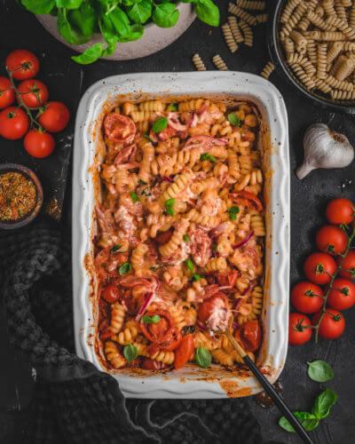 Leckerer Schafskäse mit Tomaten, Zwiebeln und Knoblauch vermischt mit Nudeln in einer Aufflaufform und Basilikum als Dekoration - abgelichtet vor dunklem Hintergrund