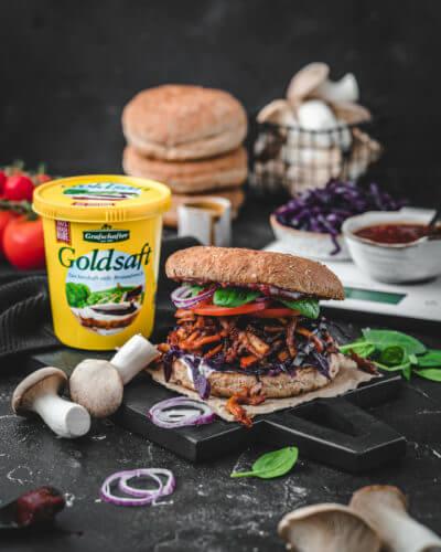 """Ein fertiger veganer Burger mit """"Pulled-Pilz"""" und BBQ Sauce, angerichtet auf einem schwarzen Holzbrett, daneben ein Töpfchen Grafschafter Goldsaft Zuckerrübensirup"""