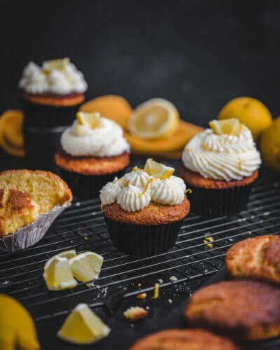 Ein durchgeschnittener Zitronenmuffin auf einem Gitter und schwarzem Untergrund, drumerhum einige Zitronencupcakes