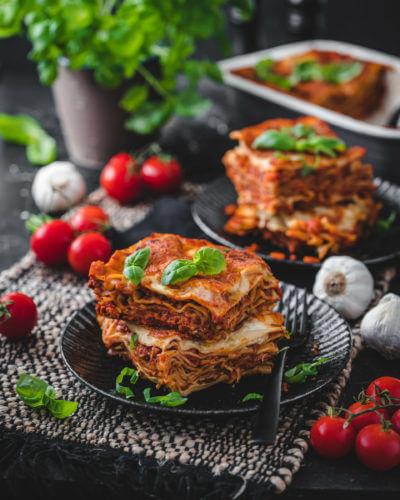 Zwei Stücken Lasagne aufgeschichtet auf schwarzen Tellern auf einem dunklen Untersetzer, drumherum wurde Basilikum, Knoblauch und Tomaten zur Dekoration verwendet