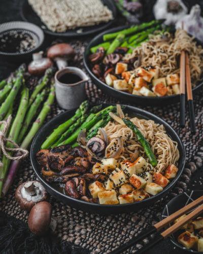 Vegetarische Ramen Suppe serviert in einem tiefen Teller zusammen mit Halloumi, grünem Spargel und Pilzen