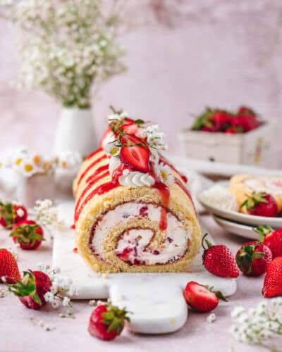 Eine Erdbeerrolle, Biskuitrolle oder auch Erdbeerroulade genannt, angerichtet auf hellem Untergrund