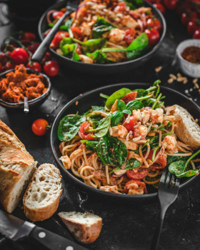 Selbstgemachter Spaghettisalat mit Pesto, Spinat und Mozzarella angerichtet in einem tiefen Teller auf dunklem Hintergrund