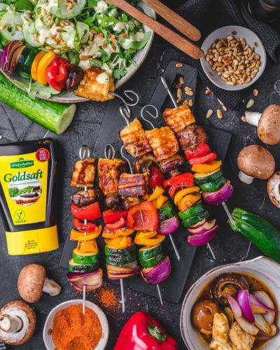 Gemüsespieße mit Halloumi und Salat angerichtet auf dunklem Untergrund