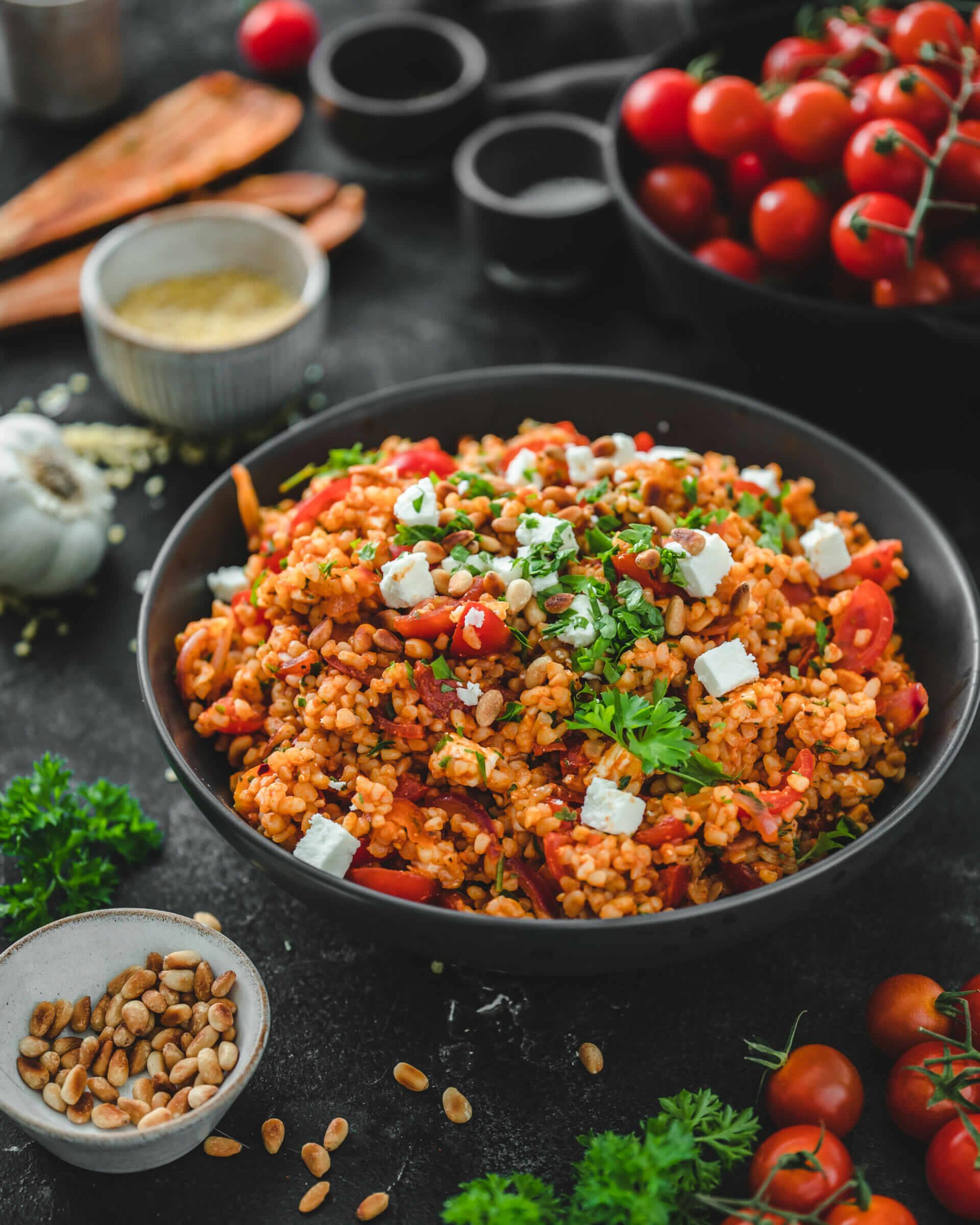 Frischer Tomaten Bulgursalat angerichtet mit Pinienkernen, Petersilie und etwas Feta in einer tiefen Schüssel